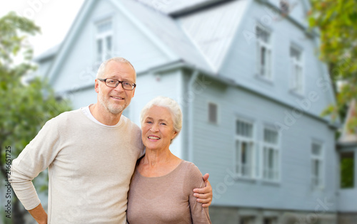 Leinwanddruck Bild old age, accommodation and real estate concept - happy senior couple hugging over house background