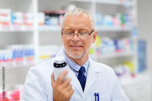 Foto Spatwand Apotheek medicine, healthcare and people concept - senior apothecary with drug at pharmacy