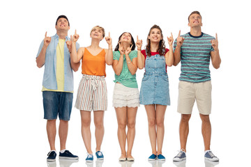 friendship and people concept - group of happy smiling friends looking and pointing fingers up over white background