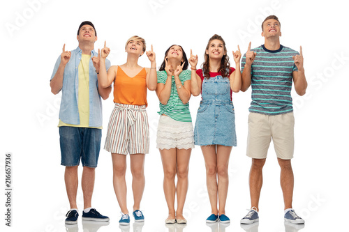 friendship and people concept - group of happy smiling friends looking and pointing fingers up over white background - 216657936
