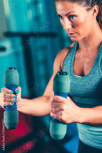 Sticker Female athlete exercising with dumbbells