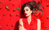 Beauty sexy model girl lying on red background with rose flowers and strawberries. Beautiful brunette young woman with long hair and perfect make-up, red seductive lips, smoky eyes. Trendy makeup - 216667925