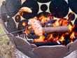 Fleisch Wurst auf einem Grillspieß über einem Lagerfeuer