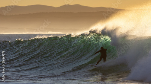 Foto Spatwand Zonsopgang The silhouette of a surfer at sunrise riding a turquoise wave