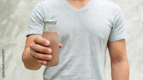 Canvas Milkshake Men holding a bottle of chocolate milk on gray background.