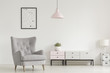 Quadro Poster above grey armchair and lamp in white living room interior with plant on cabinet. Real photo