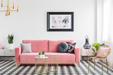 Glamour living room interior with a pink sofa, golden armchair and tables, painting and checkered tiles. Real photo - 216671348