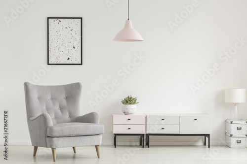 Leinwanddruck Bild Poster above grey armchair and lamp in white living room interior with plant on cabinet. Real photo