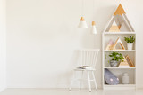 Triangles on shelves in scandi kid's room interior with white chair against the wall with copy space. Real photo - 216671576