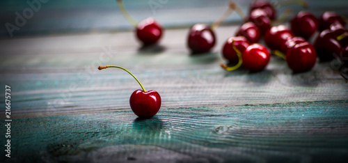 Cherry on an old wooden table. Cherry on a blue background. The old blue table on which the cherry is lying. - 216675737
