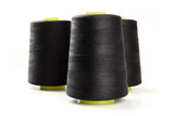 A side view of large black thread spools on a white background with copy space - 216677533
