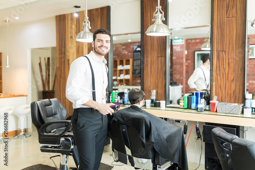Leinwandbild Motiv Barber Smiling While Hair Styling Customer In Shop