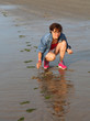 woman collects shells and clams on the beach during low tide