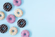 Flat lay donuts pattern on a pastel blue background with copy space for slogan.