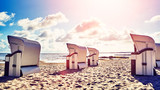 Retro stylized picture of wicker hooded basket chairs on a beach at sunset, summer holidays concept. - 216697762