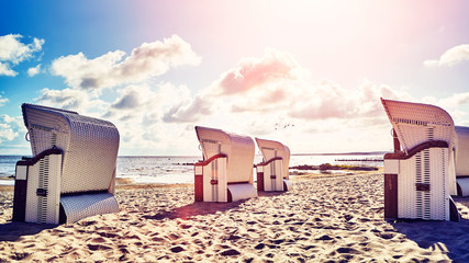 Retro stylized picture of wicker hooded basket chairs on a beach at sunset, summer holidays concept. © MaciejBledowski