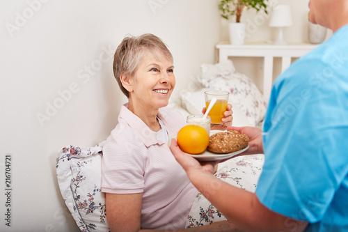 Seniorin bekommt gesundes Frühstück serviert - 216704721