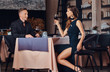 Quadro Elegantly dressed couple - handsome stylish male and charming brunette woman sitting together in a luxury restaurant.
