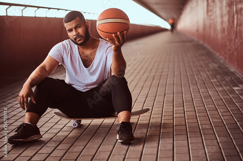 Leinwandbild Motiv Portrait of a pensive dark-skinned guy dressed in a white shirt and sports shorts holds a basketball while sitting on a skateboard on a footway under bridge.