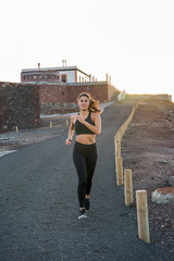 Young woman jogging on a road next to a building © pablocalvog