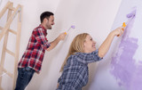 Smiling couple painting a wall and doing repair at home together