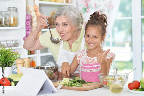grandmother and granddaughter preparing dinner  - 216717766