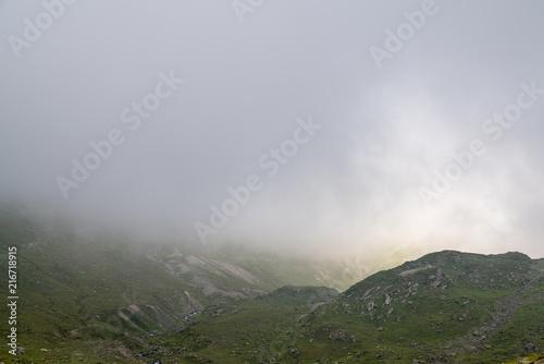 Beautiful foggy meadow. Dense fog over mountain trough the grass meadow