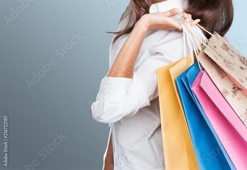 Leinwandbild Motiv Young woman with shopping bags on blurred