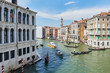 Bridge Rialto on Grand canal.  Famous landmark panoramic view Venice Italy with blue sky white cloud and many gondola boat water.