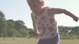 Cute 3 year old child, girl jumping on a trampoline. Slow motion. Medium close. Sunflare, campside and Realistic. - 216735149