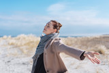Happy carefree young woman on a winter beach - 216736739
