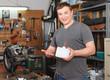Leinwanddruck Bild - Portrait of man master who is repairing motobike