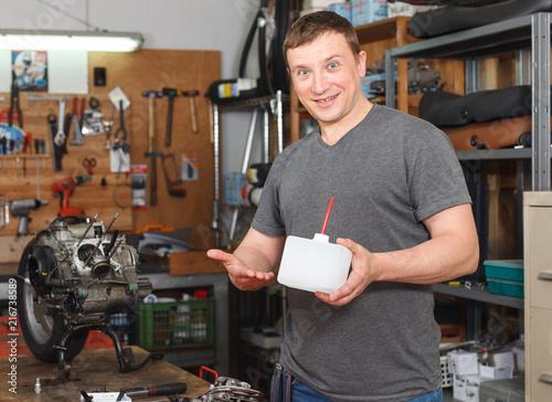 Leinwanddruck Bild Portrait of man master who is repairing motobike
