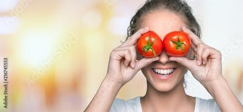 Leinwanddruck Bild Beautiful laughing woman holding two ripe tomatoes