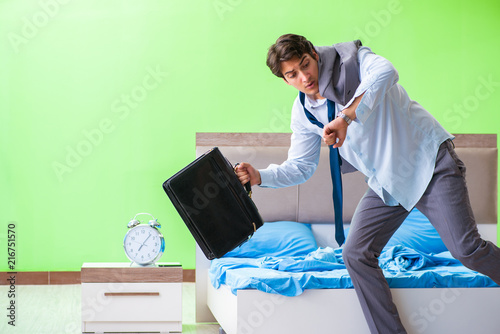 Foto Murales Employee in the bedroom being late for his job in time managemen