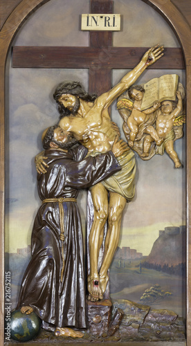 Foto Spatwand Jezus Christus REGGIO EMILIA, ITALY - APRIL 12, 2018: The relief Jesus Christ on the Cross Embracing St. Francis of Assisi in church Chiesa dei Cappuchini.