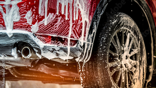 Red compact SUV car with sport and modern design washing with soap. Car covered with white foam. Car care service business concept. Car wash with foam before glass waxing and glass coating automobile. - 216758547