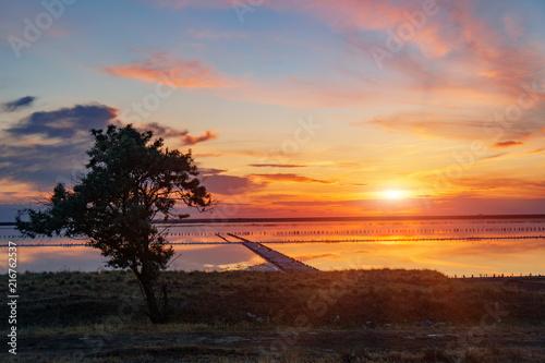 Foto Spatwand Chocoladebruin Sunset on the salt lake. Brine, salt and wooden pegs.Extraction of salt.