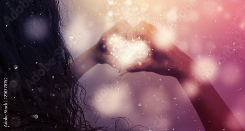 Magic emanating from the hands of a woman, a light effect in the form of hearts in the hands, glare of light, bokeh