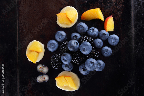 Different fruits and berries on dark background, fresh berries and pieces of banana and peach for vegan, blueberries and blackberries for breakfast, copy space - 216783581