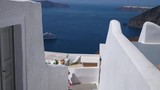 A beautiful woman in a dress walks down the white stone steps of Santorini, Greece with the blue sea in the background - 216792523