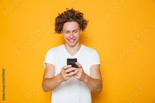 Foto Murales Brunette curly man in casual white t-shirt holding and using mobile phone, isolated over yellow background