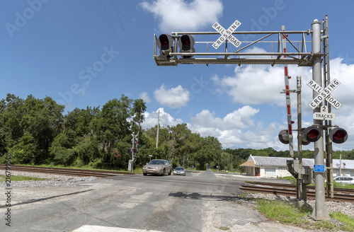 Foto Spatwand Spoorlijn Summerfield, Florida, USA, 2018. Railroad signals and track passing through North Florida countryside. Car crossing the junction.