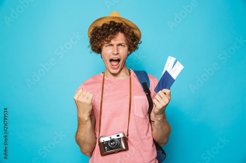 Foto Murales Image of photographer man 18-20 with curly hair wearing backpack and straw hat holding passport and tickets, isolated over blue background