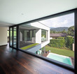 Large window in hallway of modern villa overlooking the private pool