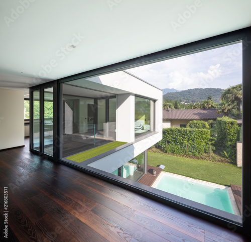 Large window in hallway of modern villa overlooking the private pool - 216803571
