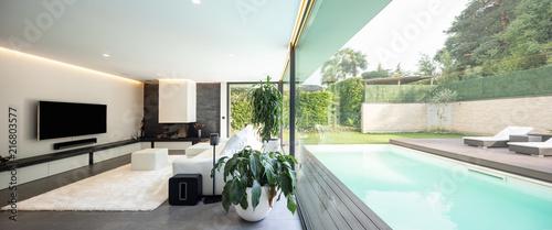 Leinwanddruck Bild Modern living room overlooking the garden and swimming pool.