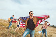 handsome young man holding usa flag and walking by field with friends during trip