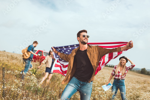 Foto Murales handsome young man holding usa flag and walking by field with friends during trip