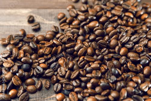 Foto Spatwand Koffiebonen Grains of coffee scattered on a wooden brown background